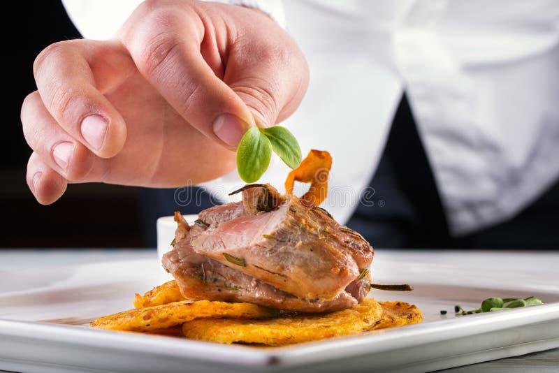 Kock i hotell- eller restaurangkökmatlagning, endast händer Förberedd köttbiff med potatis- eller selleripannkakor royaltyfria bilder