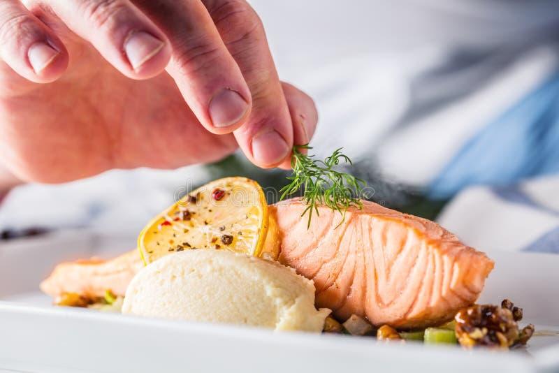 Kock i hotell- eller restaurangkökmatlagning, endast händer Förberedd laxbiff med dillgarnering royaltyfri bild