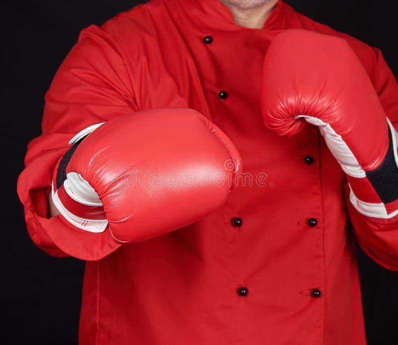Kock i röda likformig- och läderboxninghandskar som står i en kugge royaltyfria bilder