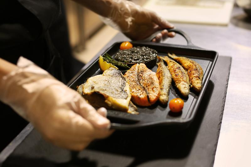 Kock med det läckra stekte fiskuppläggningsfatet arkivfoton