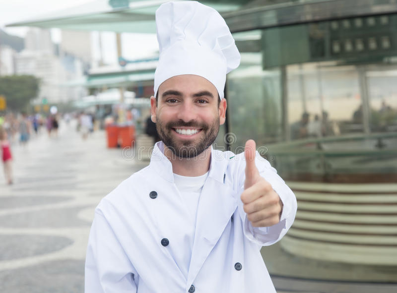 Kock med skäggvisningtummen framme av en restaurang arkivbilder