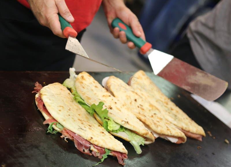 kock, medan laga mat piadinaen kallade också Spianata i italienare l arkivfoton