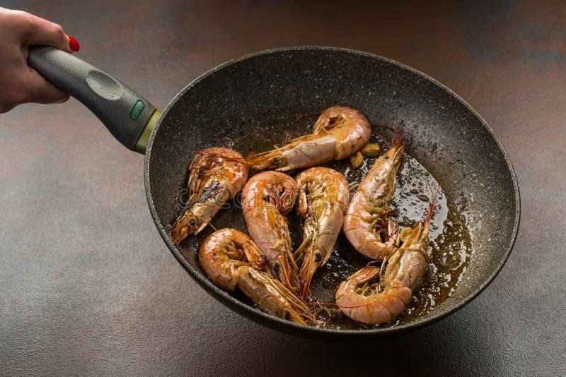 kock på arbete handen rymmer en varm panna med stekt räka process av förberedelsen av tigerräkor royaltyfria bilder