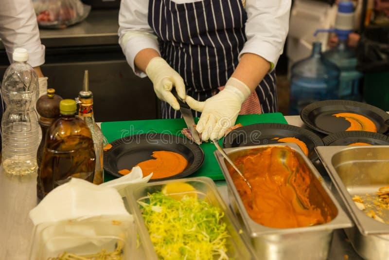 Kock Preparing Plates i restaurangkök royaltyfria bilder