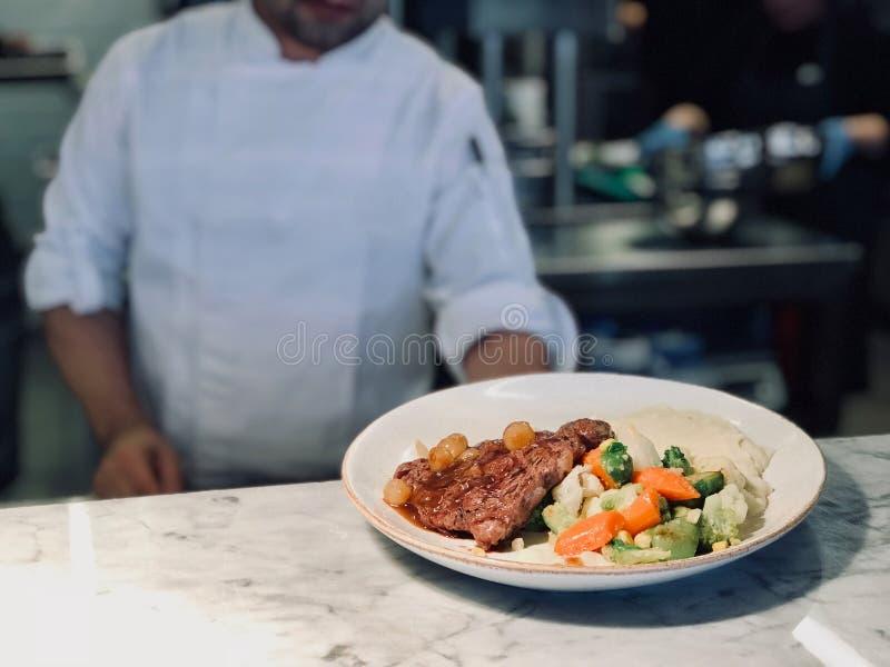 Kock Ready som tjänar som New York biff med schalottenlöklökar och grönsaker på restaurangkök arkivfoto