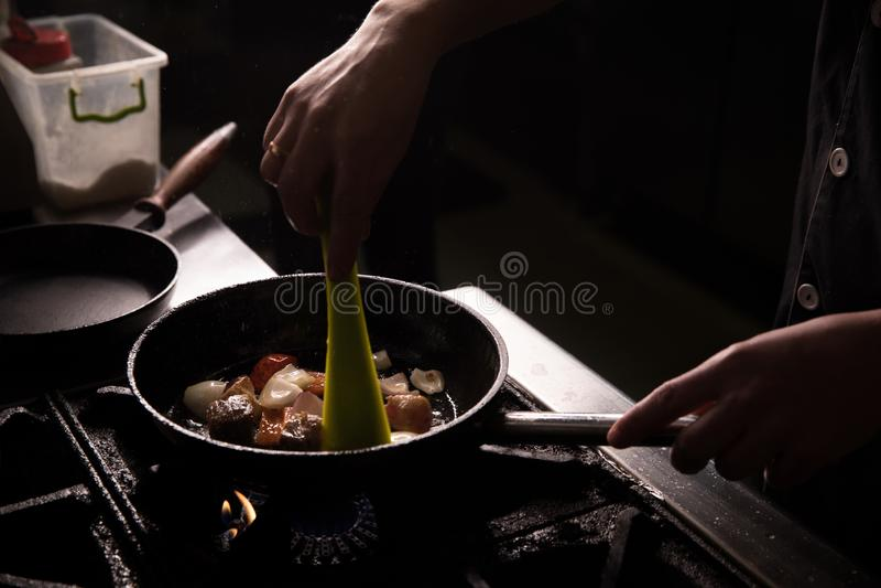 Kock In Restaurant Kitchen som förbereder matmörkerbakgrund royaltyfria foton