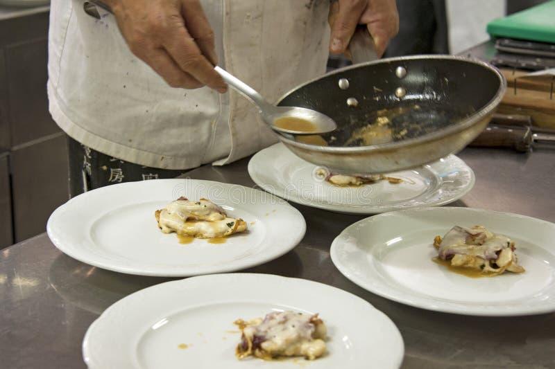 Kock som dekorerar den läckra maträtten arkivbild
