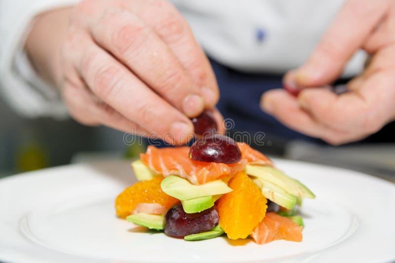 kock som dekorerar den läckra maträtten arkivfoton