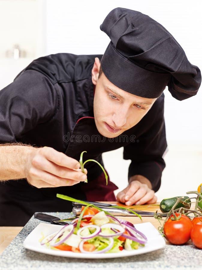 kock som dekorerar läcker plattasallad arkivbild