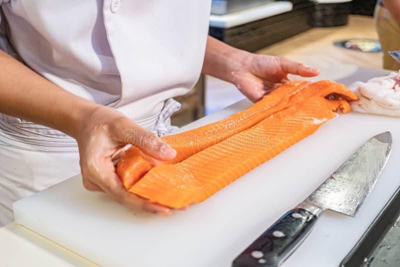 Kock som förbereder och klipper den nya laxen i japansk restaurang fotografering för bildbyråer