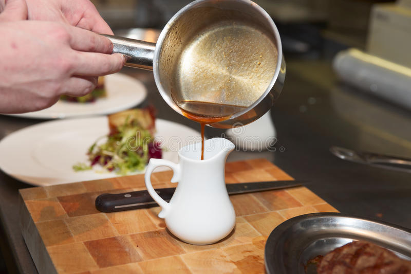kock som förbereder sås royaltyfri foto
