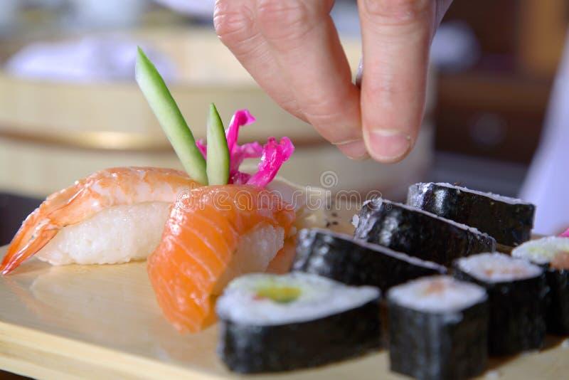 kock som förbereder sushi arkivbild