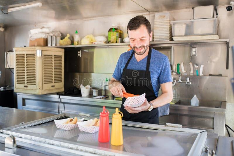 Kock som förbereder varmkorvar fotografering för bildbyråer