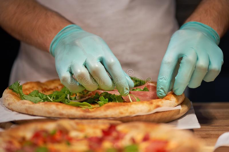 Kock som g?r en parma eller prosciuttoskinka italiensk pizza i ett slut upp sikt av hans h?nder som f?rl?gger k?ttet royaltyfri bild