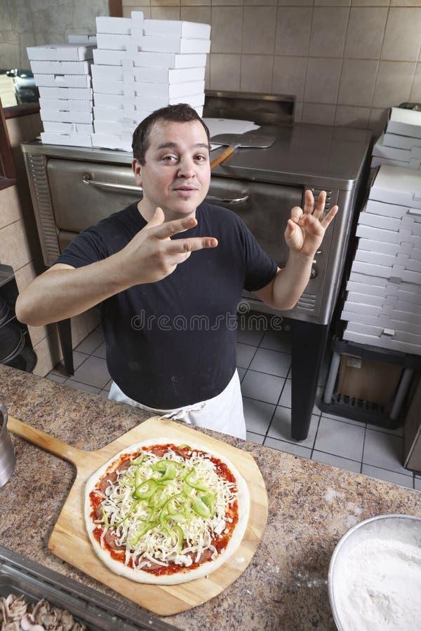 kock som gör pizza royaltyfria bilder
