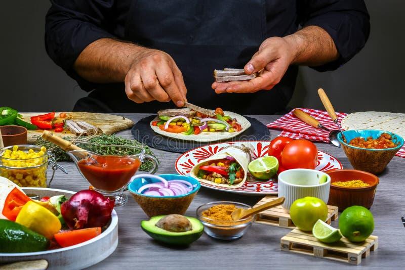 Kock som gör tortillan Mexicanska kokkonstmellanmål som lagar mat snabbmat för kommersiellt kök royaltyfria foton