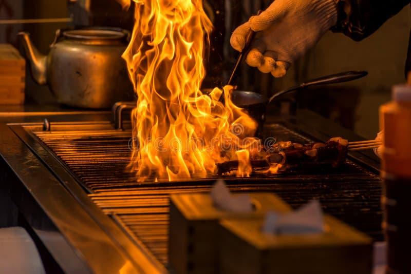 kock som grillar bbq med flamman av bränningen i restaurang arkivfoton