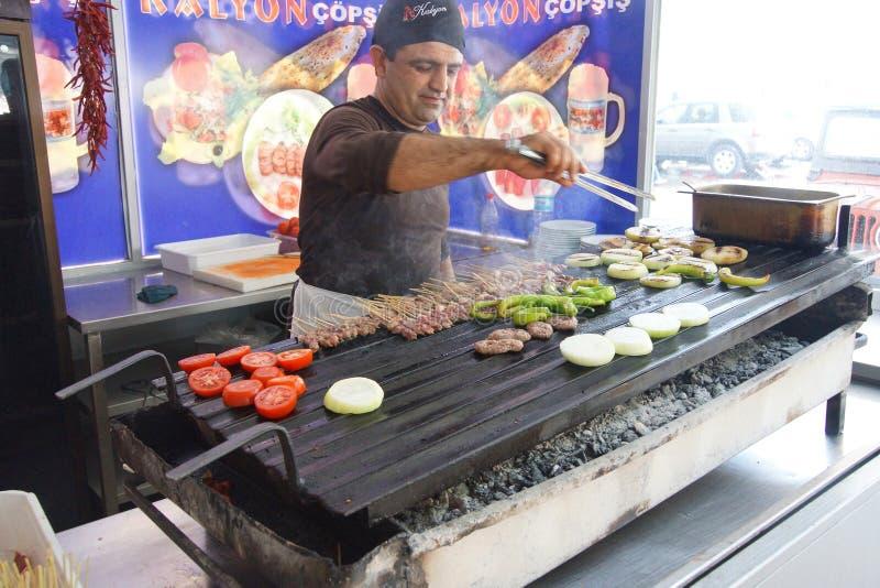 Kock som grillar korvar och kebabsteknålar royaltyfri fotografi