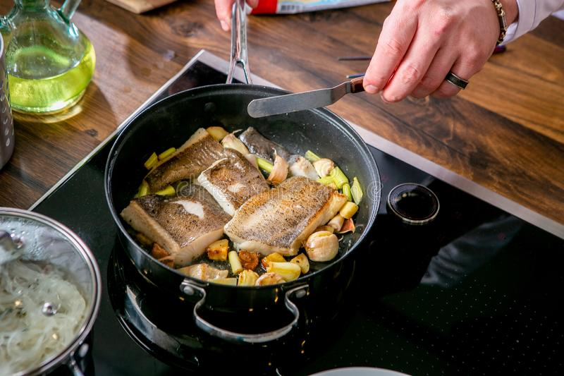 Kock som grillar stycken av hälleflundra i en panna Mästarklass i köket Processen av matlagning Begrepp med mänskliga fotspår tut royaltyfri fotografi