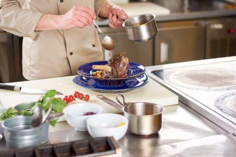 Kock som häller med sauselammlägget royaltyfria bilder