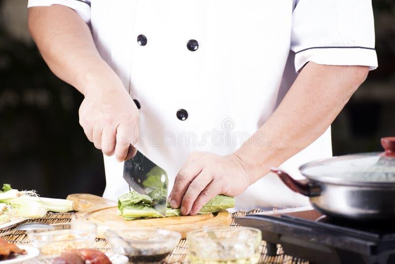 Kock som hugger av grönsaken, innan att laga mat nudeln arkivfoto