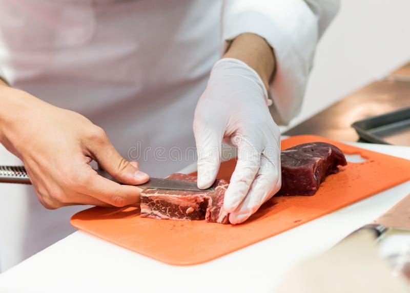 Kock som klipper nytt rått kött med kniven i köket, kock som klipper nötkött på ett bräde arkivfoton