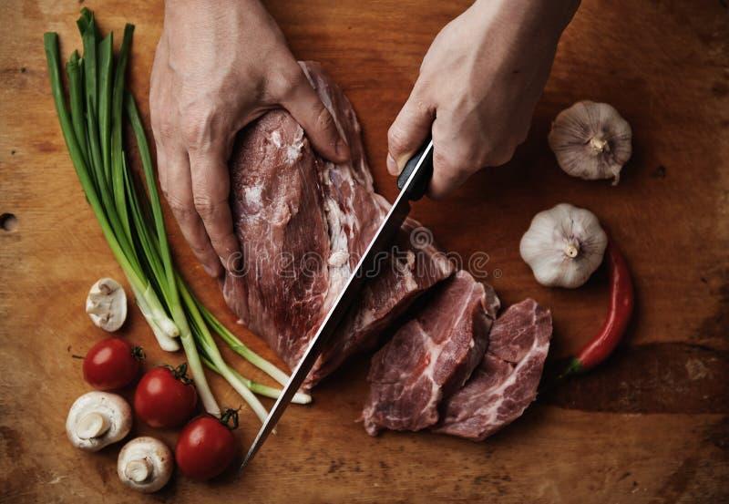 Kock som klipper rått kött royaltyfria bilder