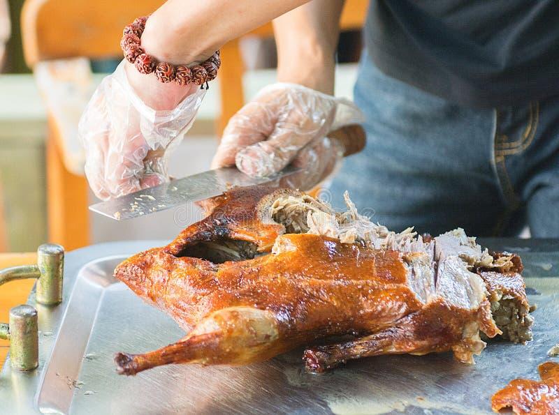 Kock som klipps upp en saftig ljus och smaklig matr?tt f?r and Peking, h?rligt, som ?r klar att leverera kocken arkivfoto