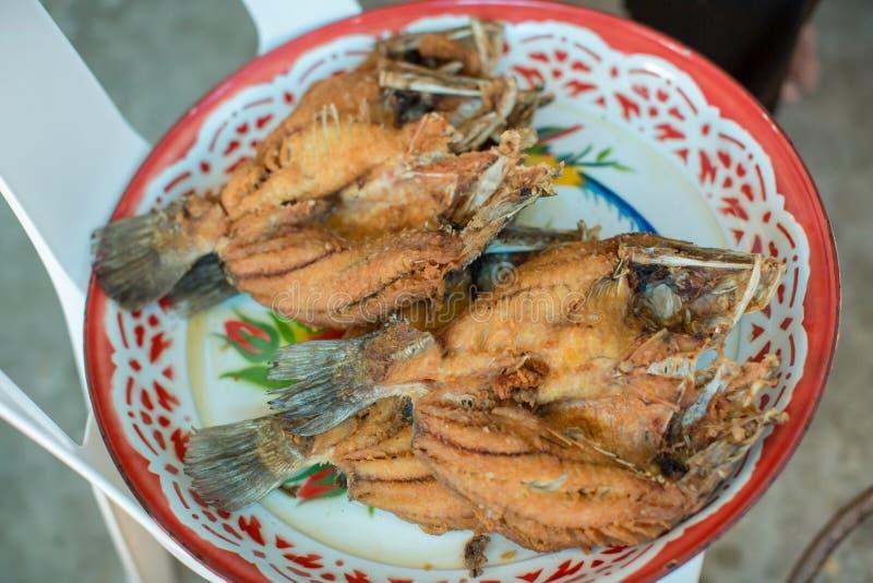 Kock som lagar mat den friterade fisken i den stora pannan till den kinesiska bankettmatf?rberedelsen fett fr?n trans.-fett begre fotografering för bildbyråer