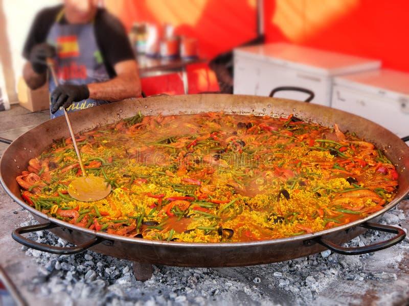 Kock som lagar mat enorm spansk paella arkivfoto