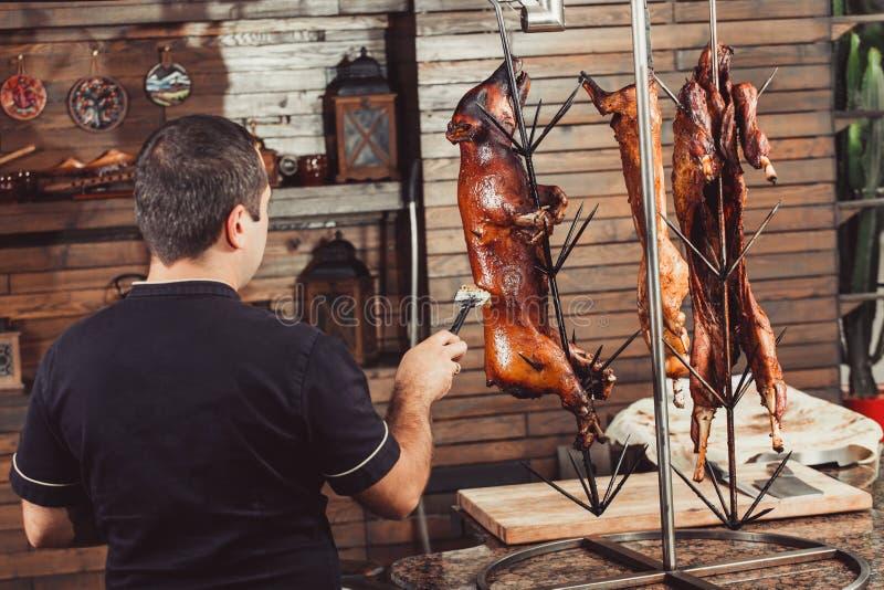 Kock som lagar mat grillat griskött för varmt tandoorgaller besegrar varm meat besegrar varm meat arkivbild