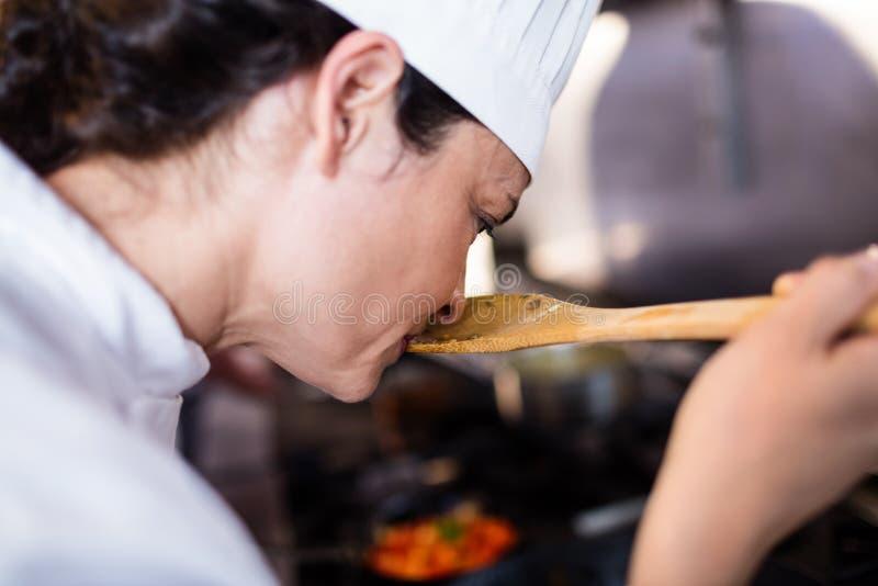 Kock som luktar mat i köket arkivbild