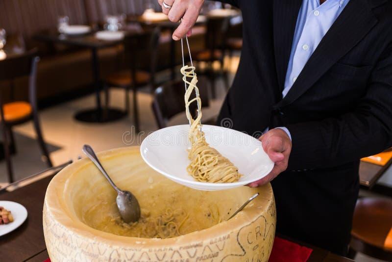 Kock som pläterar trevligt spagetticarbonara i osthjul på den vita plattan royaltyfri bild