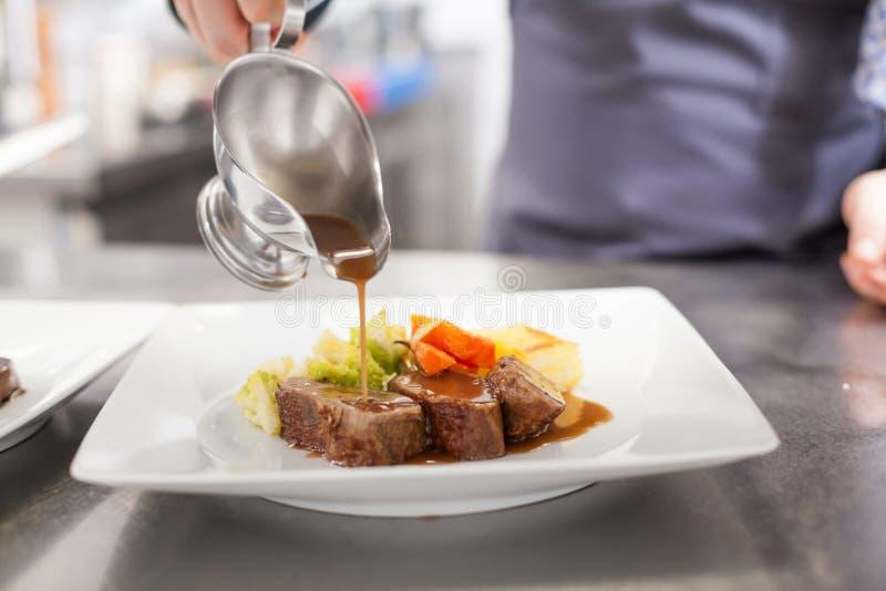 Kock som pläterar upp mat i en restaurang royaltyfria bilder