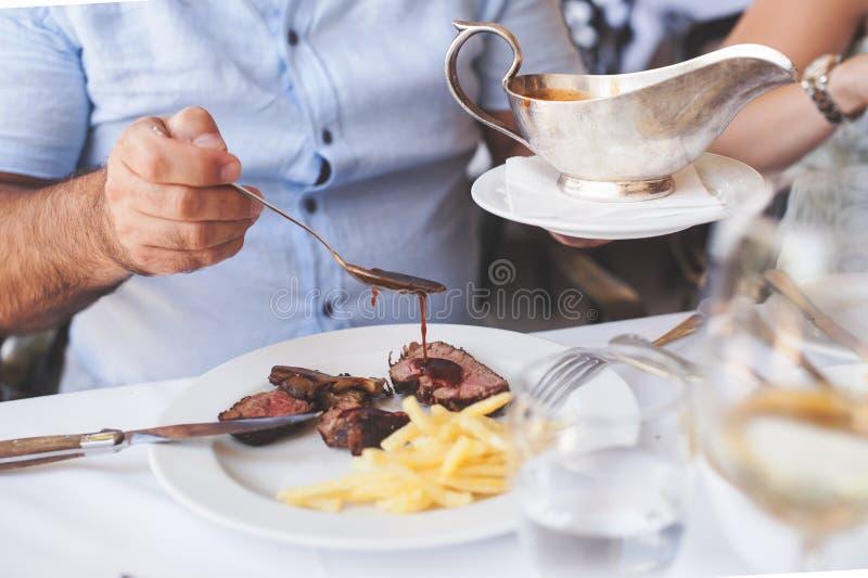 Kock som pläterar upp mat i en restaurang som häller en sky eller en sås över köttet, innan att tjäna som det till kunden fotografering för bildbyråer