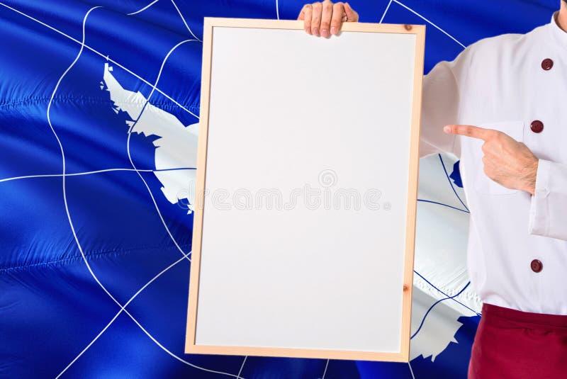 Kock som rymmer den tomma whiteboardmenyn på Antarktis flaggabakgrund Laga mat den bärande likformign som pekar utrymme för text royaltyfri foto