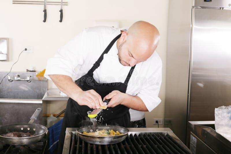 Kock som sätter grated parmesan till en italiensk pasta royaltyfria bilder