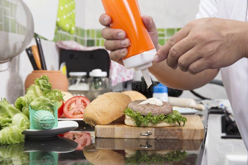 Kock som sätter majonnäs på hamburgarebullen arkivfoton