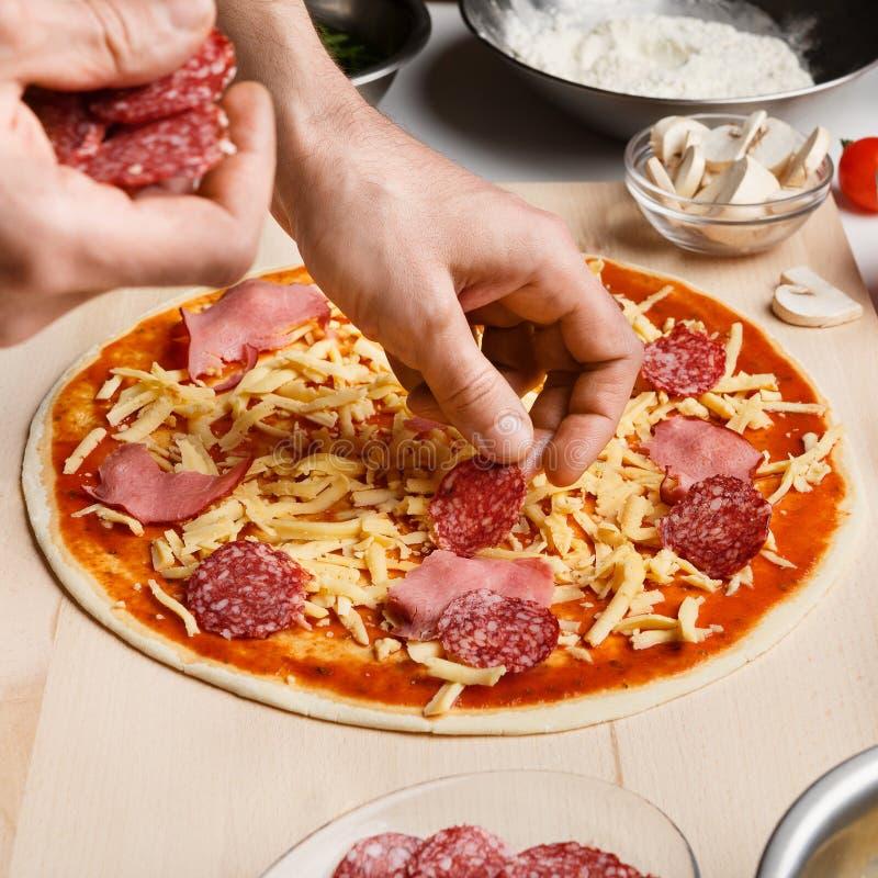 Kock som sätter salami över ost på rå pizza royaltyfria foton