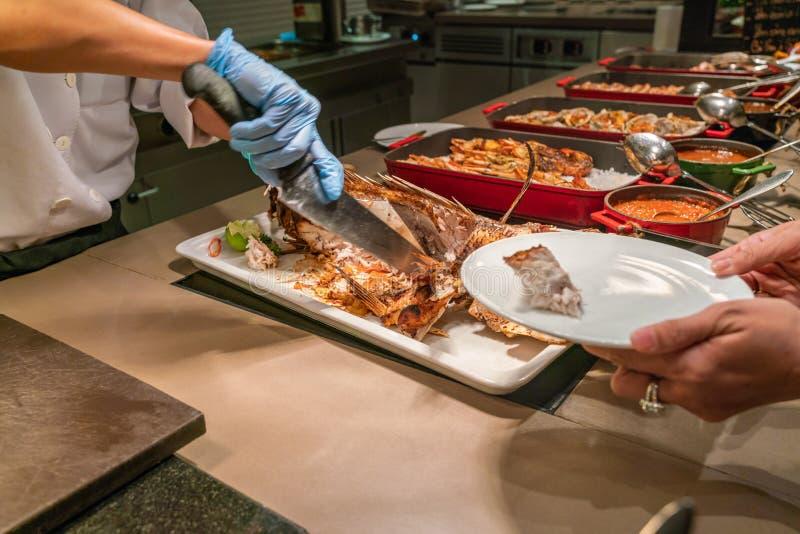 Kock som skivar och klipper den grillade fisken arkivfoto