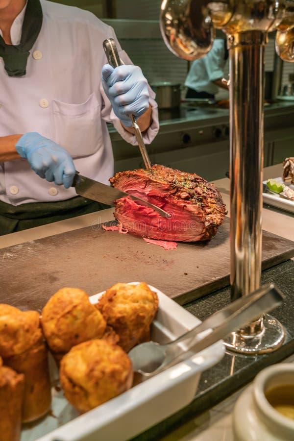 Kock som skivar och klipper grillad nötköttbiff i bufférestaurangen royaltyfri bild