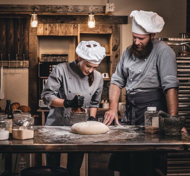Kock som undervisar hans assistent att baka brödet i ett bageri arkivfoto
