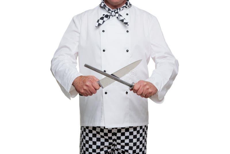 Kock som vässar hans kniv. arkivbild