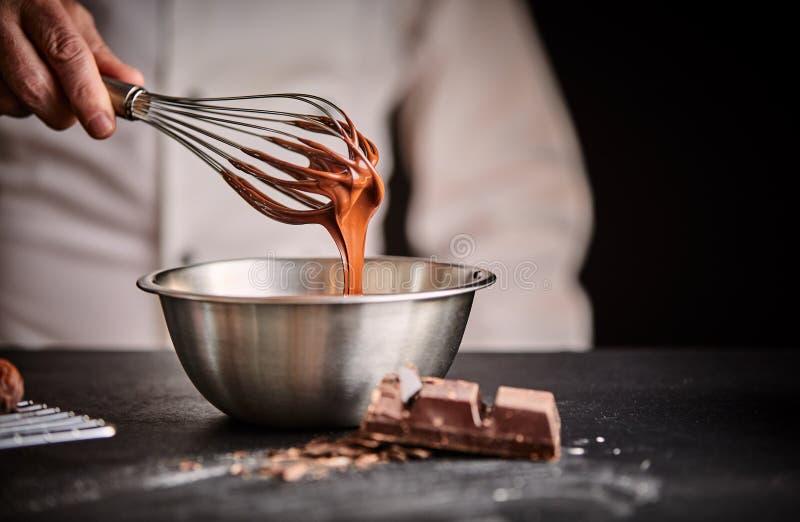 Kock som viftar smältt choklad i en plastbunke royaltyfria foton
