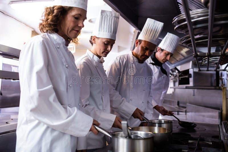 Kockar som förbereder mat i kök royaltyfria bilder