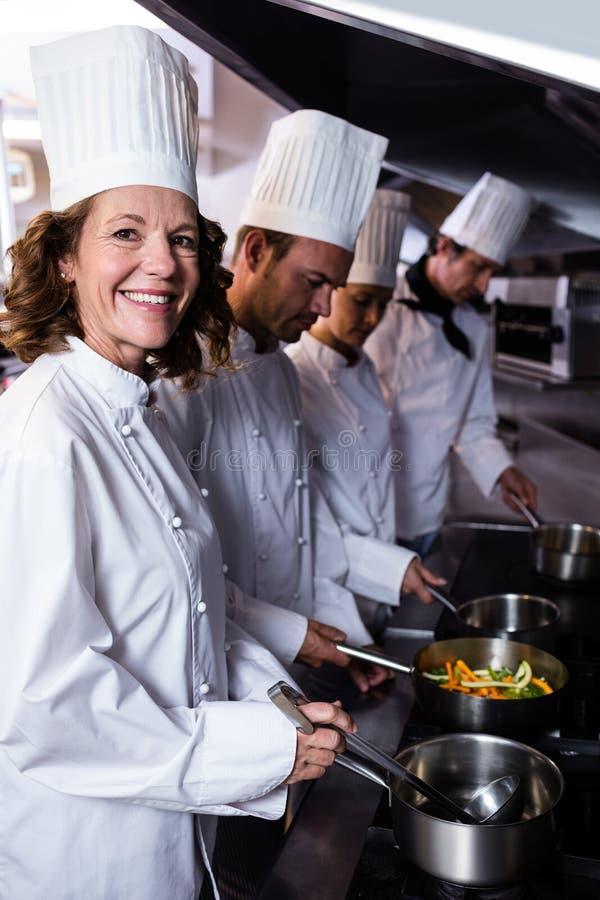 Kockar som förbereder mat i kök arkivbilder