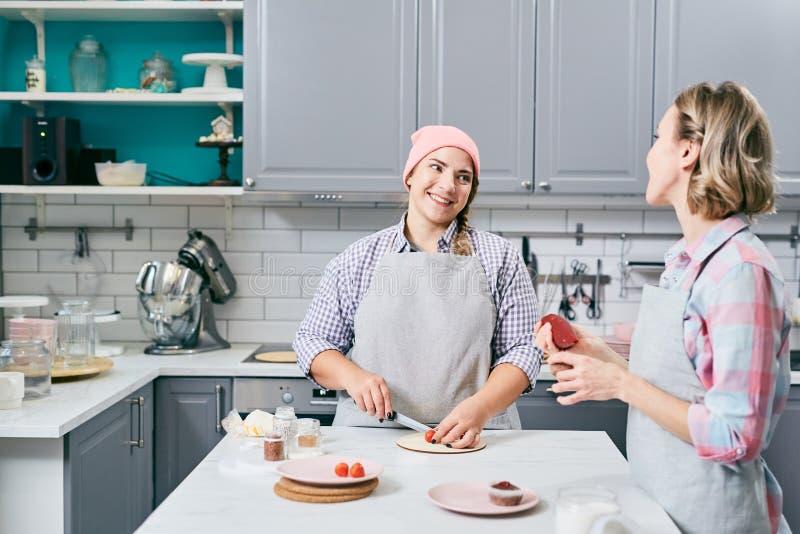 Kockar som pratar i kök arkivfoto