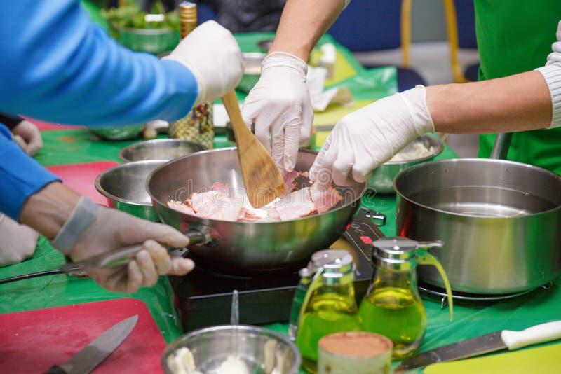 Kockar som steker bacon i pannan Ingredienser och kök bearbetar på vitbakgrund royaltyfri foto