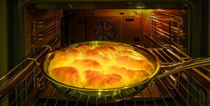 Kocken bakar pajer med äpplen för ferien i ugnen arkivfoton