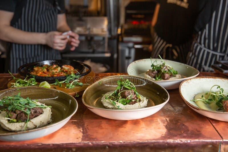 Kocken dekorerar fläskkarrébiff med gräsplan arkivbild